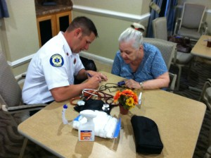 Lt. Ryan Hathaway with Okeechobee County Fire Rescue taking vital signs for seniors.